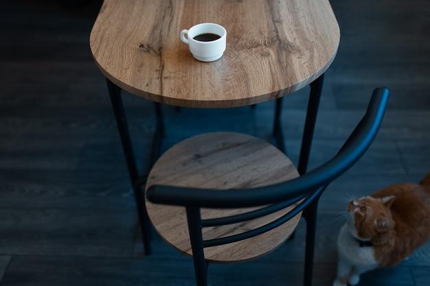 薄茶色の木製の机の上のエスプレッソの小さな白いカップのクローズアップ