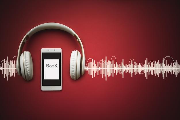 오디오 트랙이 있는 빨간색 배경에 스마트 폰, 헤드폰 및 오디오북의 클로즈업. 오디오, 들어보세요. 오디오북 개념입니다.