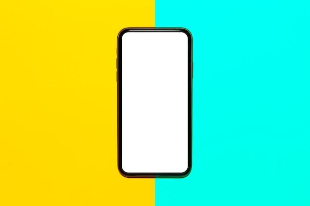 노란색과 청록색 색상의 표면에 빈 화면이있는 스마트 폰의 클로즈업