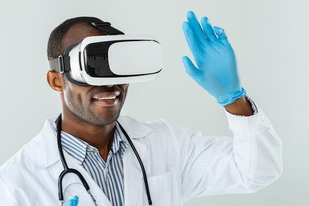 Крупным планом улыбается афро-американский врач в очках vr, выражая радость