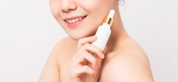 흰색 벽에 고립 된 로고, 바디 로션, 화장품 병 및 제품 템플릿을 들고 웃는 아시아 여자 손의 닫습니다