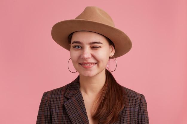 チェッカージャケットと茶色の帽子を身に着けている、遊び心のある点滅、笑顔の魅力的な若い女性のクローズアップ。ピンクの背景に分離されたカメラを見てください。