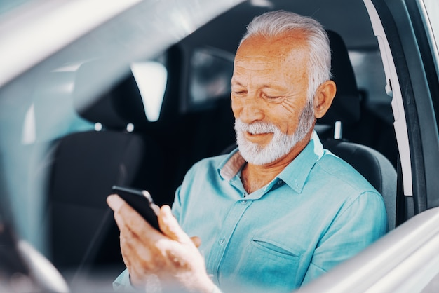 차에 앉아있는 동안 열린 창에 팔 메시지를 작성하거나 읽기위한 스마트 폰을 사용하여 수염 수석 미소의 닫습니다.