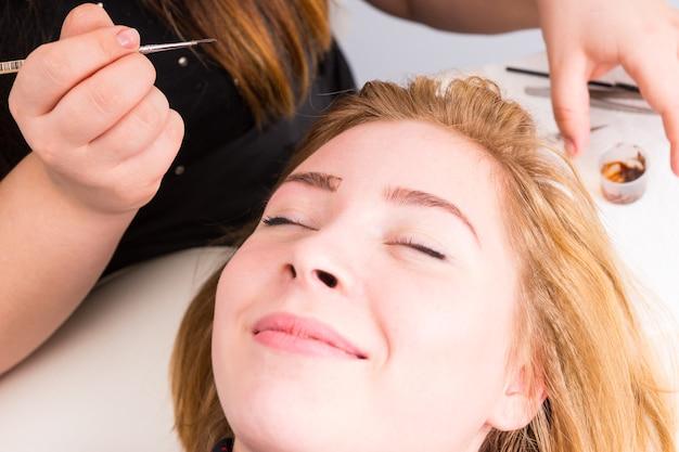 눈썹 그루밍 스파 트리트먼트 중 웃는 금발 클라이언트 클로즈업 - 에스테티션은 메이크업 브러쉬와 짙은 갈색 냄비를 배경으로 들고 있습니다.