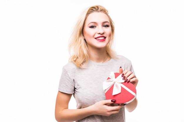 Крупный план улыбается женщина blondie держит сердце в форме подарочной коробке