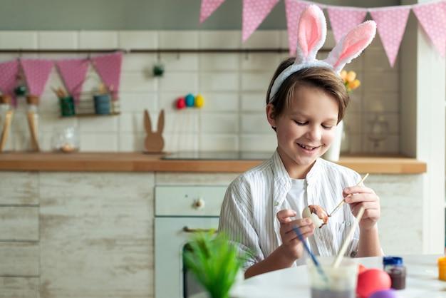 부엌에서 테이블에 앉아 부활절 달걀 그림 웃는 소년의 닫습니다.