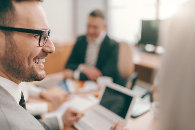 フォーマルな服装と会議で座っている眼鏡のビジネスマンを笑顔のクローズアップ。チームワークは夢を実現させます。