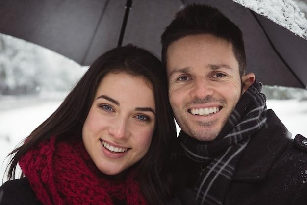 冬の森の中で笑顔のカップルのクローズアップ