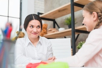 Close-up of smiling female psychologist looking at blonde girl
