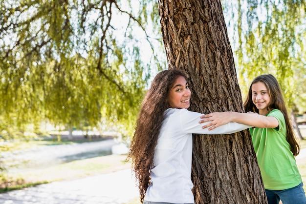 Крупный план улыбающихся девушек, держа друг друга за руку, обнимая большое дерево в парке