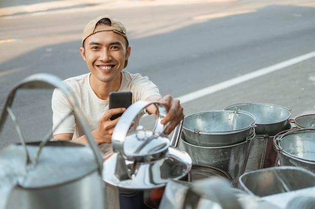 家電店でやかんの写真を撮るときに電話カメラを使用して笑顔の男性の売り手のクローズアップ