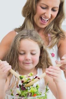 笑顔の母と娘の野菜サラダを混ぜるのを閉じます