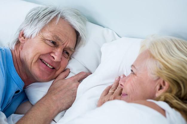 ベッドで寝ている笑顔の年配のカップルのクローズアップ