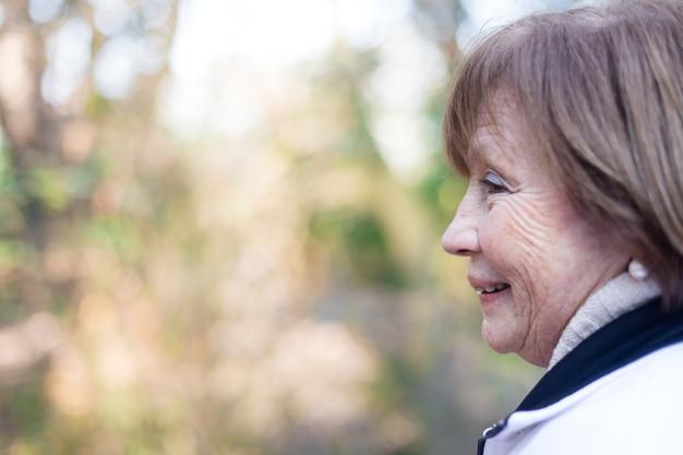 Крупным планом улыбается старший женщина в парке