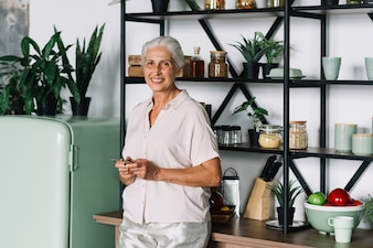 Close-up of smiling senior woman using mobile standing in kitchen