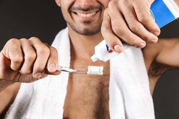 孤立して立って、歯ブラシに歯磨き粉を置く彼の肩にタオルで笑顔の上半身裸の男のクローズアップ