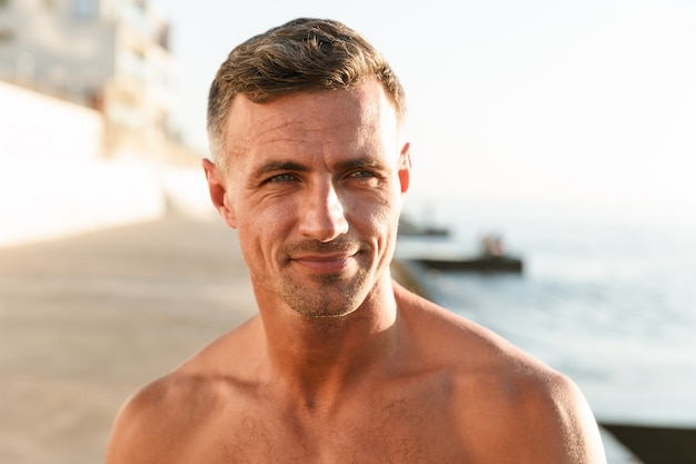 ビーチで笑顔の上半身裸のスポーツマンのクローズアップ