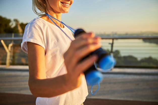 Крупным планом улыбающаяся спортивная дама со скакалкой в руке, стоя на улице