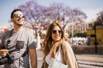 Close-up of smiling tourist young couple standing on street