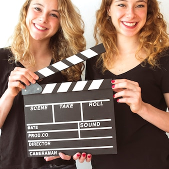 Close-up of smiling wins sister holding clapperboard in hands