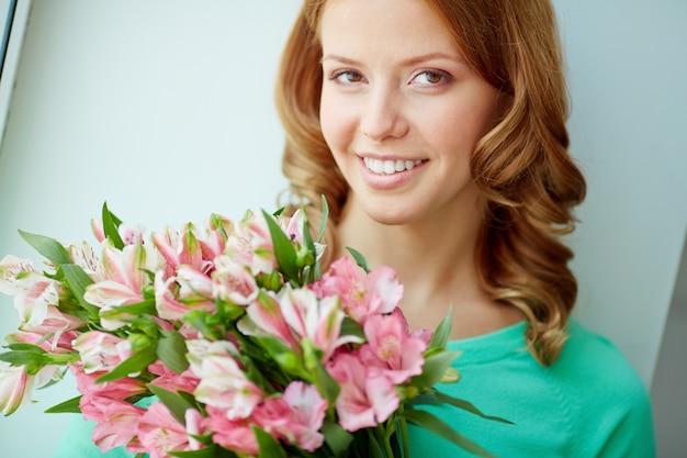Крупным планом улыбается женщина держит букет