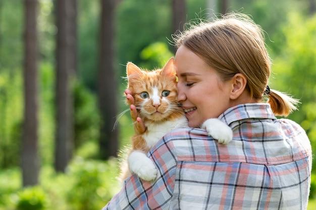 チェックシャツを着た笑顔の女性のクローズアップは、優しさで抱きしめ、抱きしめ、屋外で国内の興奮した悲しい猫を愛しています。