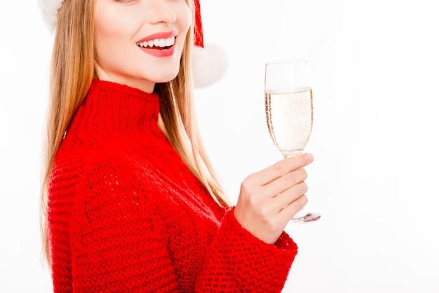 Крупным планом улыбается женщина в красном свитере, держащая бокал шампанского