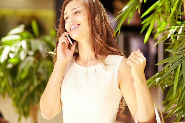 Крупным планом улыбается женщина с мобильным телефоном