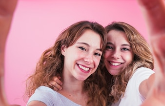 Close-up of smiling young female friends taking self portrait