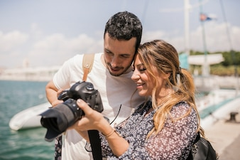 Close-up of smiling young tourist couple looking at slur camera