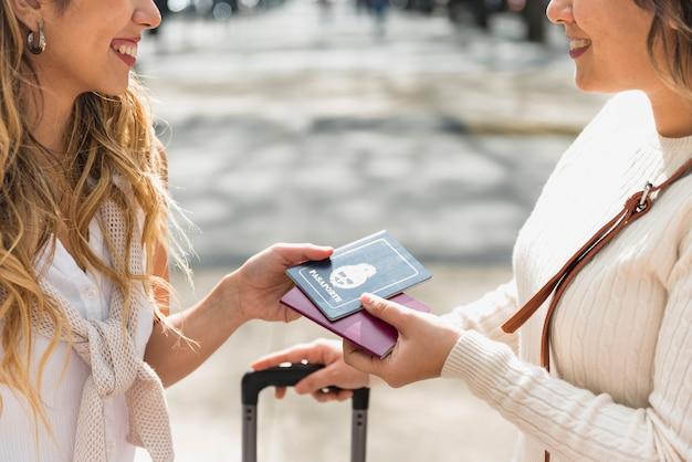 屋外でお互いに自分のパスポートを見せて笑顔の若い女性のクローズアップ