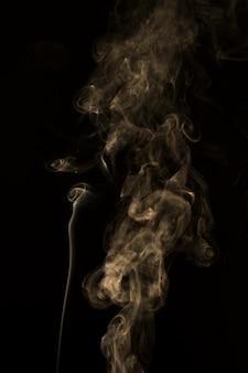 黒の背景に広がる煙のクローズアップ
