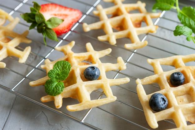 ブルーベリー、イチゴとワイヤーラック上の柔らかいウィーンのワッフルのクローズアップ