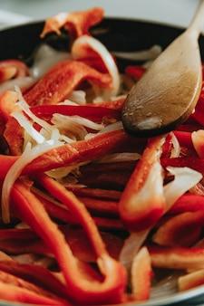 Закройте несколько перцев на сковороде деревянной ложкой с красочным цветовым пространством