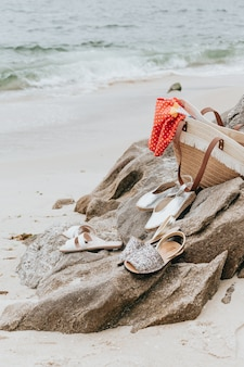 晴れた日のビーチでいくつかのサンダルとサマーバッグのクローズアップ