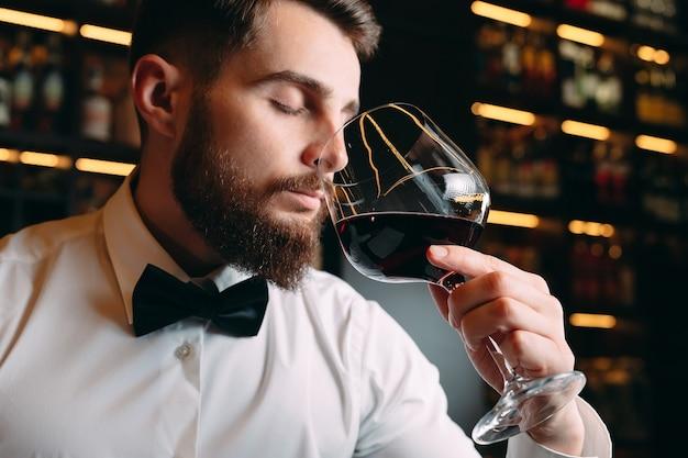 Крупным планом человек сомелье, нюхающий вино в стекле