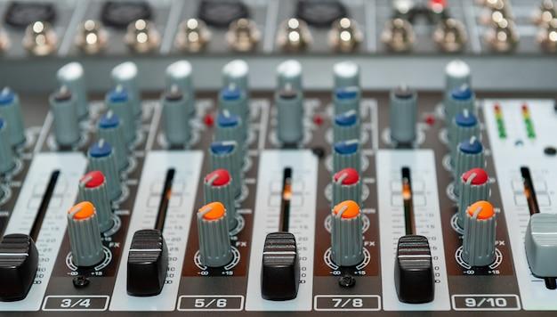 Крупным планом звуковой микшерный пульт. детали комнаты звукорежиссера.