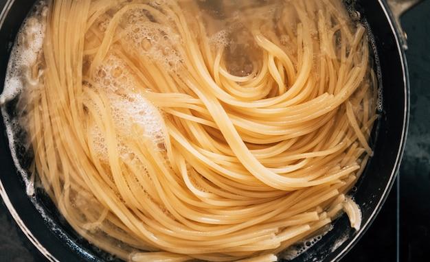 Крупный план спагетти макароны в кипящей воде в стальной кастрюле.