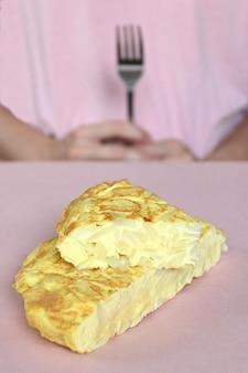 スペインのオムレツ、背景、ピンクの背景とコピースペースにフォークを持つ女性のクローズアップ。
