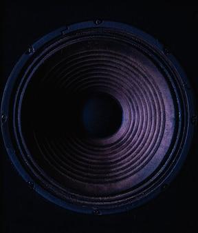 色付きの照明と黒の背景にスピーカー膜のクローズアップ。