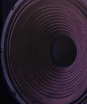 컬러 조명이 있는 검은색 배경의 스피커 멤브레인 클로즈업.