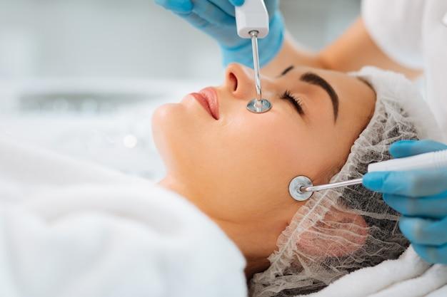 Крупный план специального устройства, прижатого к коже во время микротоковой терапии.