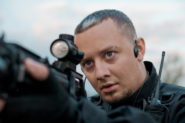アサルトライフルを狙う黒い制服を着た特殊部隊の兵士のクローズアップ