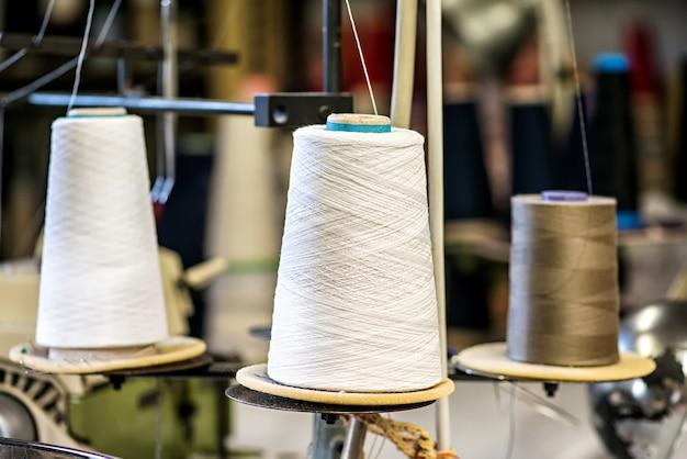 Крупный план катушек с хлопковой нитью на промышленной швейной машине на фабрике трикотажной одежды