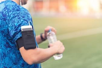 朝の暖かい光の中で水のボトルを使ってスポーツマンの手を閉じます。