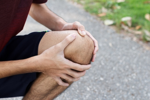 実行後の膝の怪我を実行しているスポーツの痛みで苦しんでいるスポーツ男のクローズアップ。