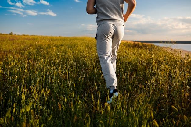 日の出フィールドでジョギング陽気な男のクローズアップ。