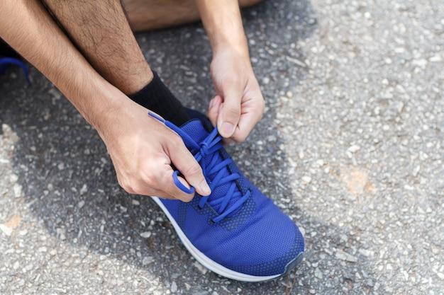 Крупный план спортсмена. перед тренировкой он завязывает кроссовки на кроссовки.
