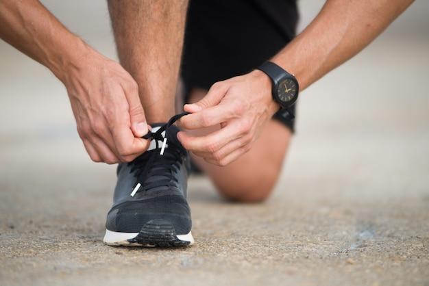 Крупный план спортсмена, связывающего кроссовки