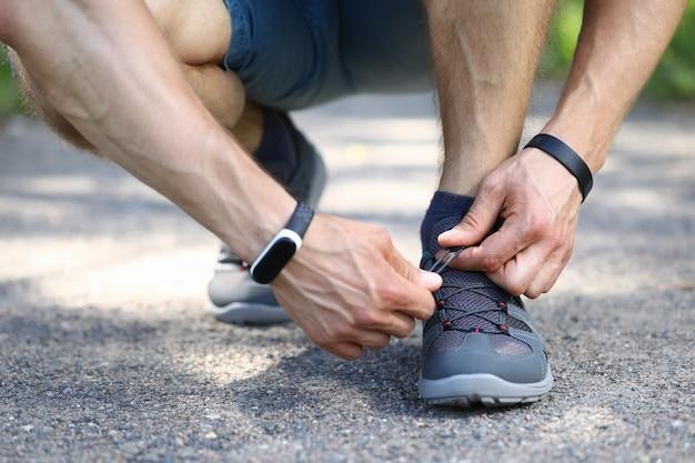 Крупный план спортивных рук человека мужского пола, связывающих шнурки. стильные серые кроссовки для бега. человек готов к утренней пробежке. городская улица. тренировка и тренировка для концепции сильного тела